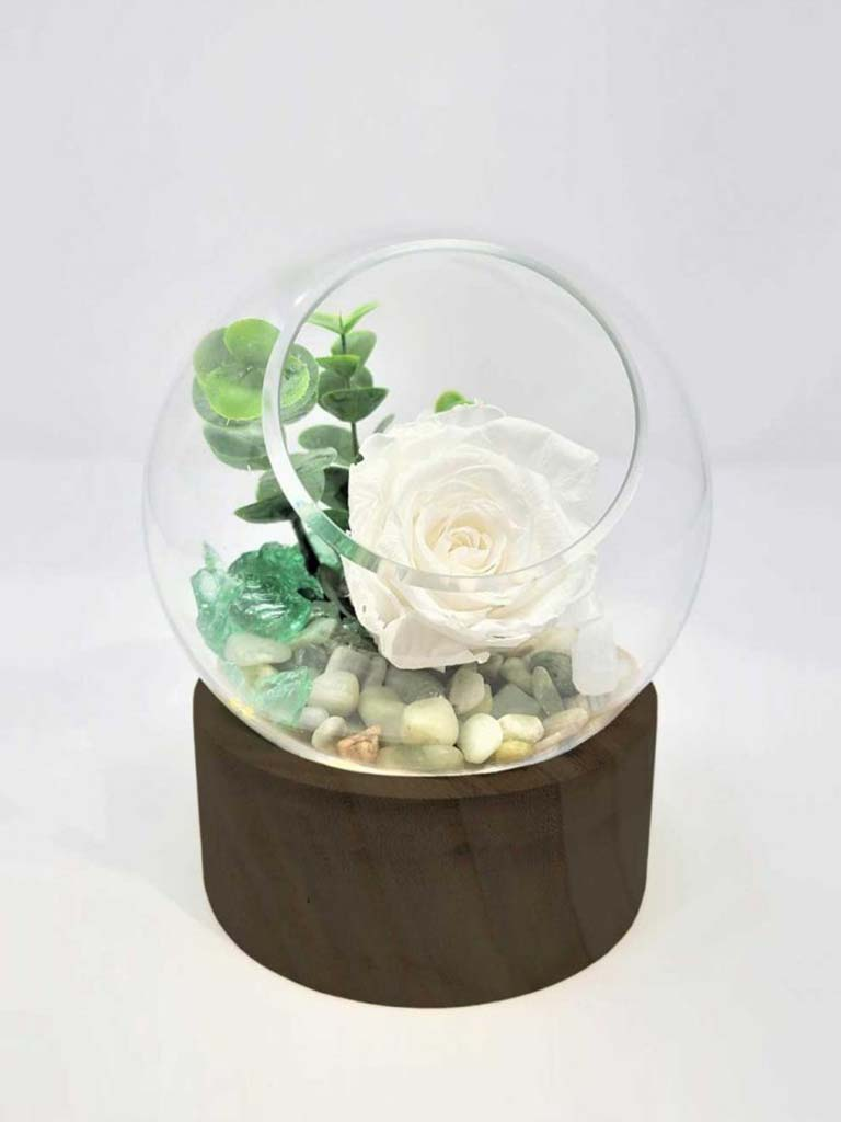Rose éternelle blanche dans un pot en verre et bois